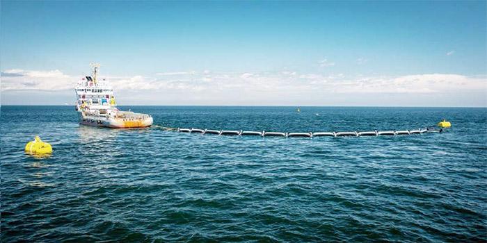 荷蘭少年Boyan Slat計畫將100公里長的攔油索固定在海床,被動攔截洋流漂送的塑膠廢棄物。圖中漂浮的攔油索為今年6月設置在大西洋的測試原型。